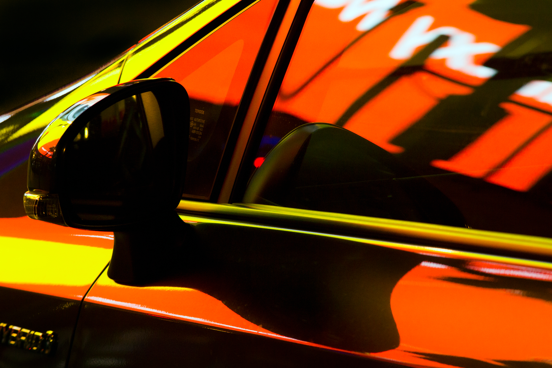 Car at night lit by advertising from the Autos series by street photographer Nick Turpin